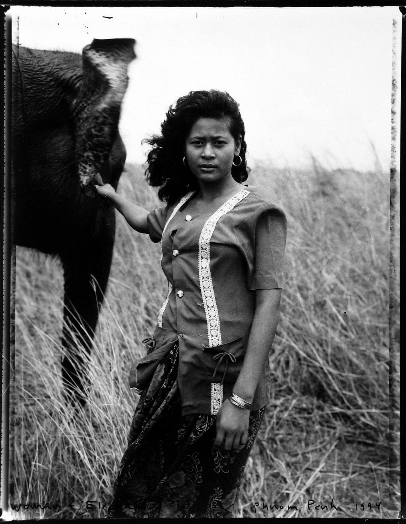 Bill Burke - Woman and elephant, Phnom Penh, 1994 - Howard Greenberg Gallery