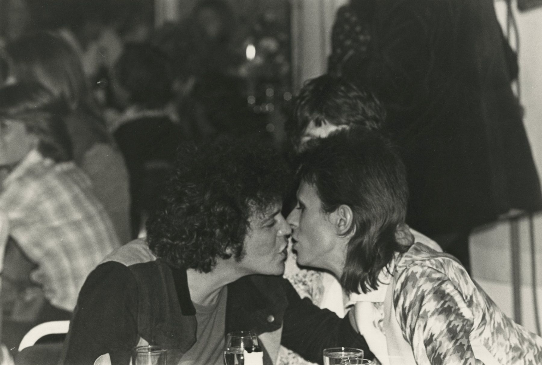 Mick Rock - Lou Reed and David Bowie, seated by Mick Jagger, kiss at the Cafe Royal, after Ziggy Stardust's last live performance at Hammersmith Odeon in London, 1973 - Howard Greenberg Gallery - 2018