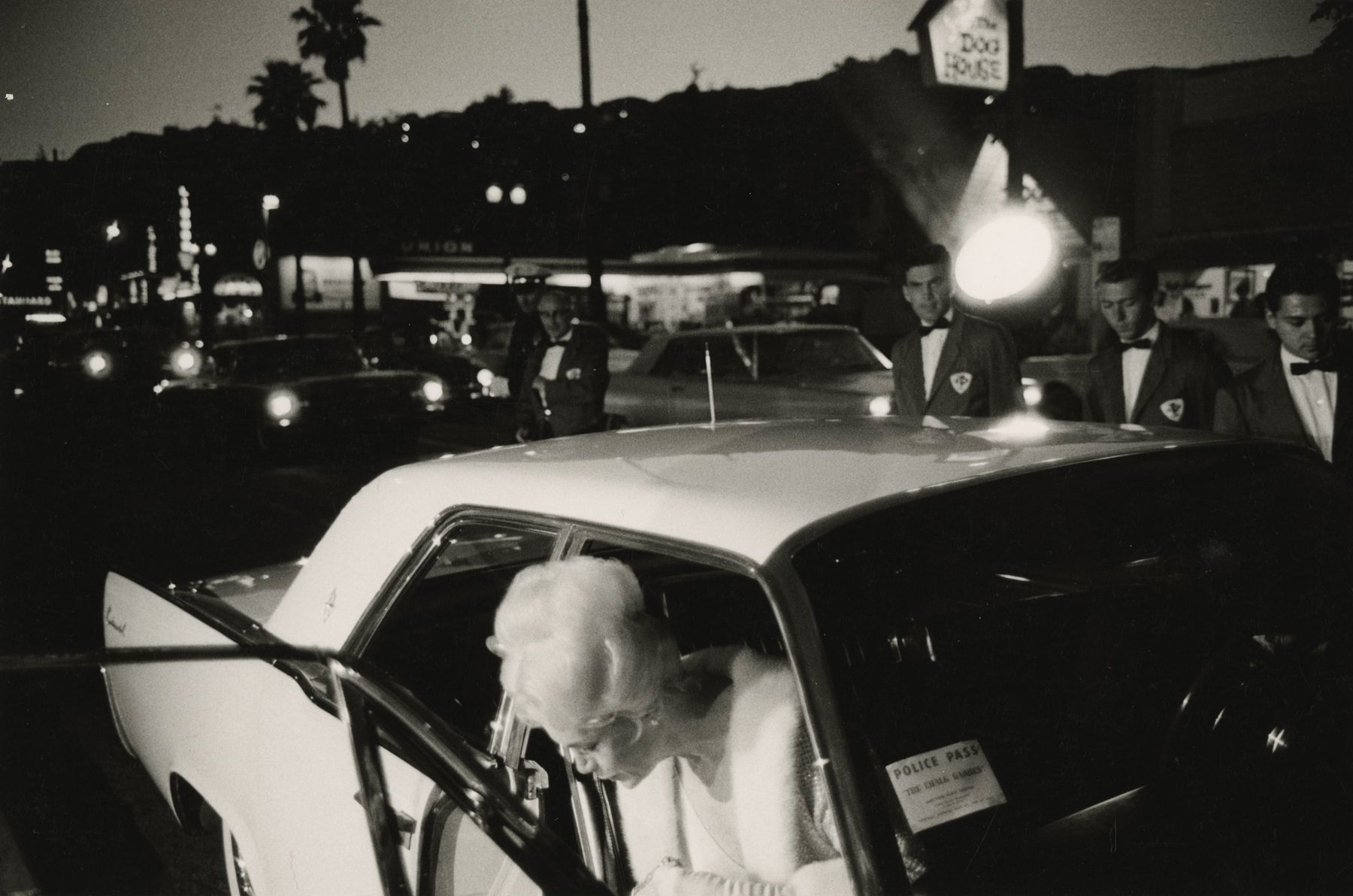 Bruce Davidson - An Affluent Woman Getting Out of a White Car in Hollywood, Los Angeles, California, 1960s - Howard Greenberg Gallery - 2018