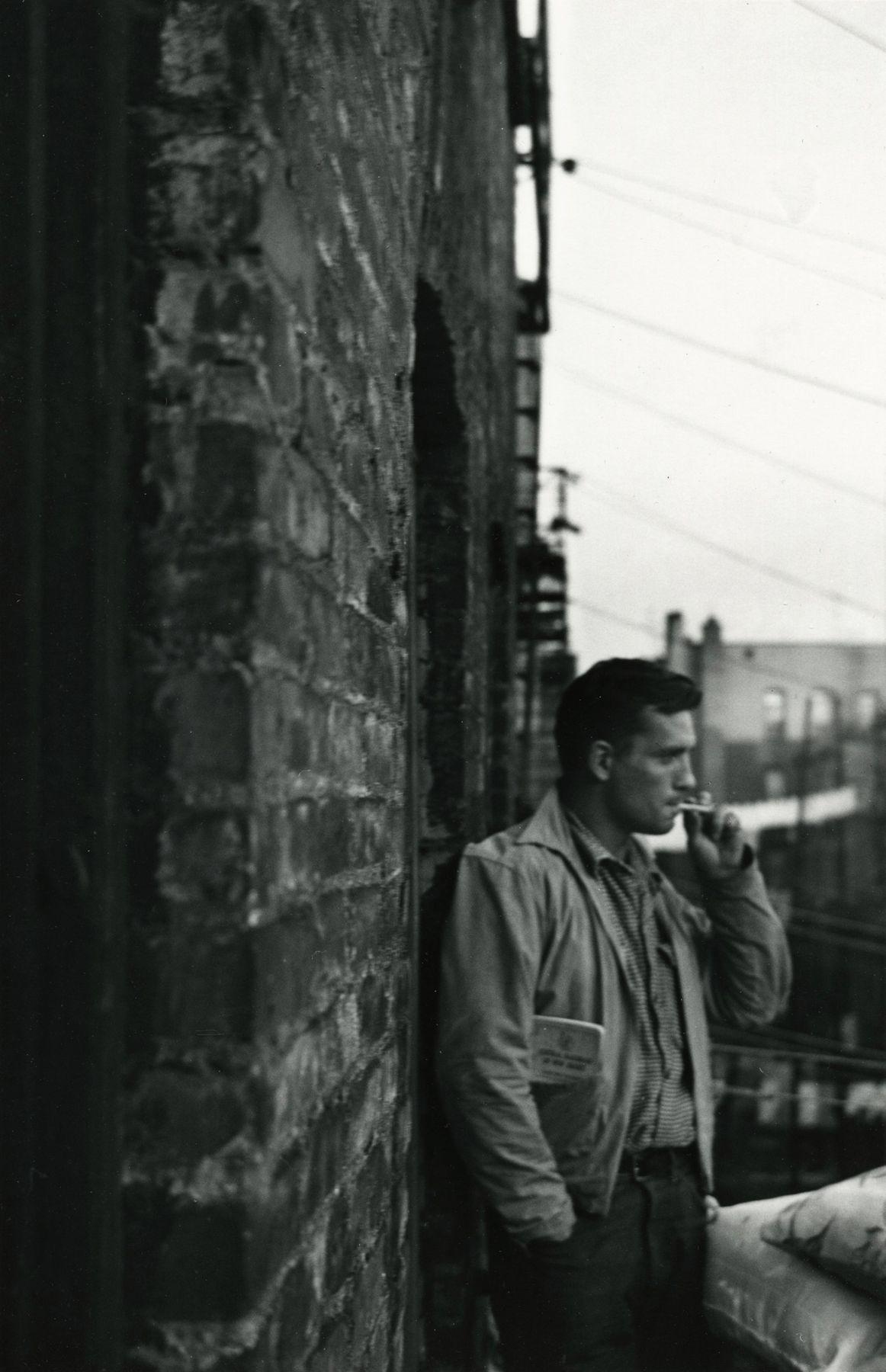 Allen Ginsberg - Heroic portrait of Jack Kerouac with R.R Brakeman's manual in pocket, fire-esape 206 E. 7th Street, NY, 16-Dec-86- Howard Greenberg Gallery