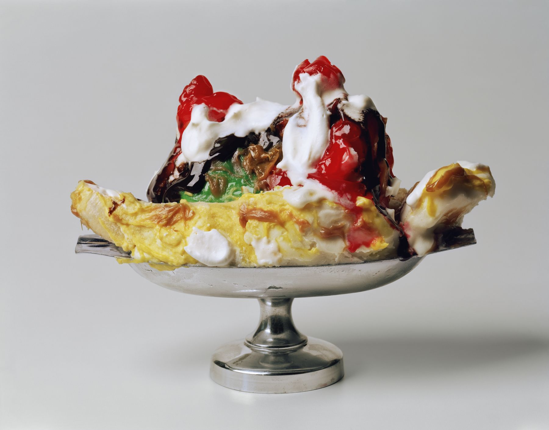 Photograph by Sharon Core of a banana split sundae in a silver dish arranged to look like the sculpture by Claes Oldenburg.