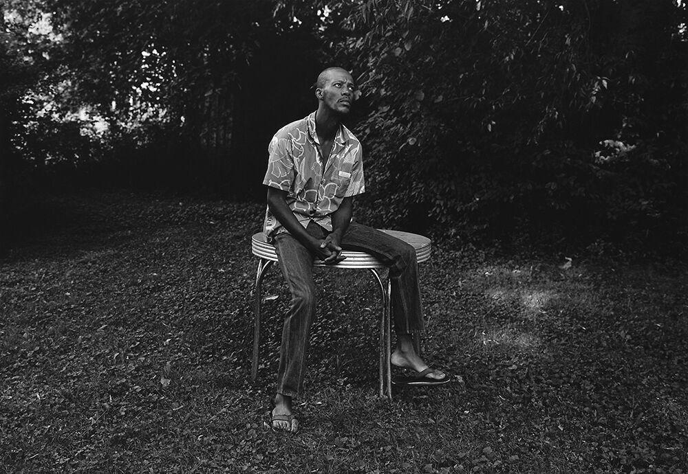 Mark Steinmetz,Knoxville, TN (man sitting on table),1991.Gelatin silver print, 20 x 24 inches.