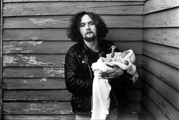 Man Holding Baby with Clenched Fist, 1986, 14 x 11 inches, gelatin silver print