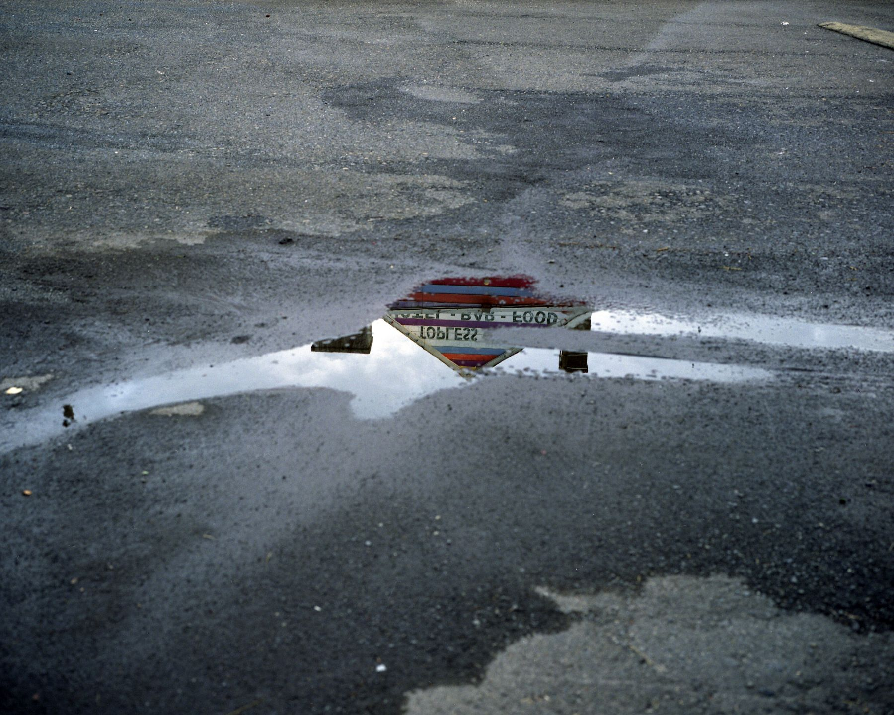 Topless bar reflected in puddle, Doylestown, Pennsylvania, 2010. Archival pigment print, 30 x 40 inches.