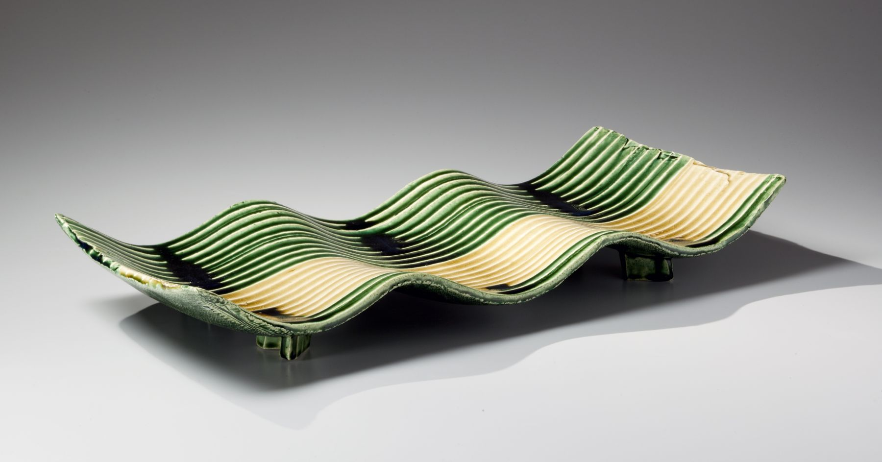 Suzuki Tetsu (b. 1964), Undulating rectangular platter with carved horizontal linear stripes covered with pooling green and yellow glazes