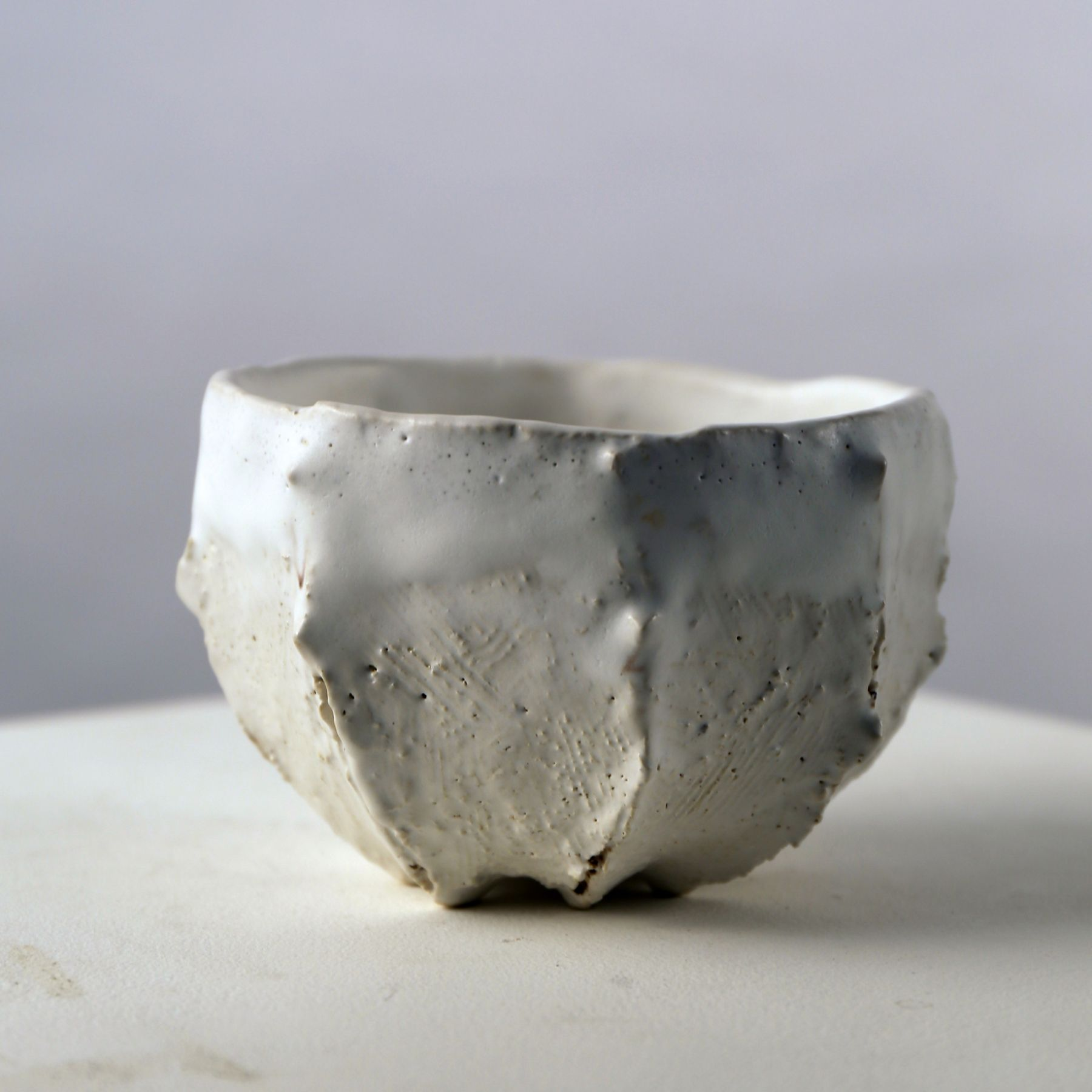 Matte white-glazed ribbed teabowl with small protrusions and interior pool of crackled glaze, 2007