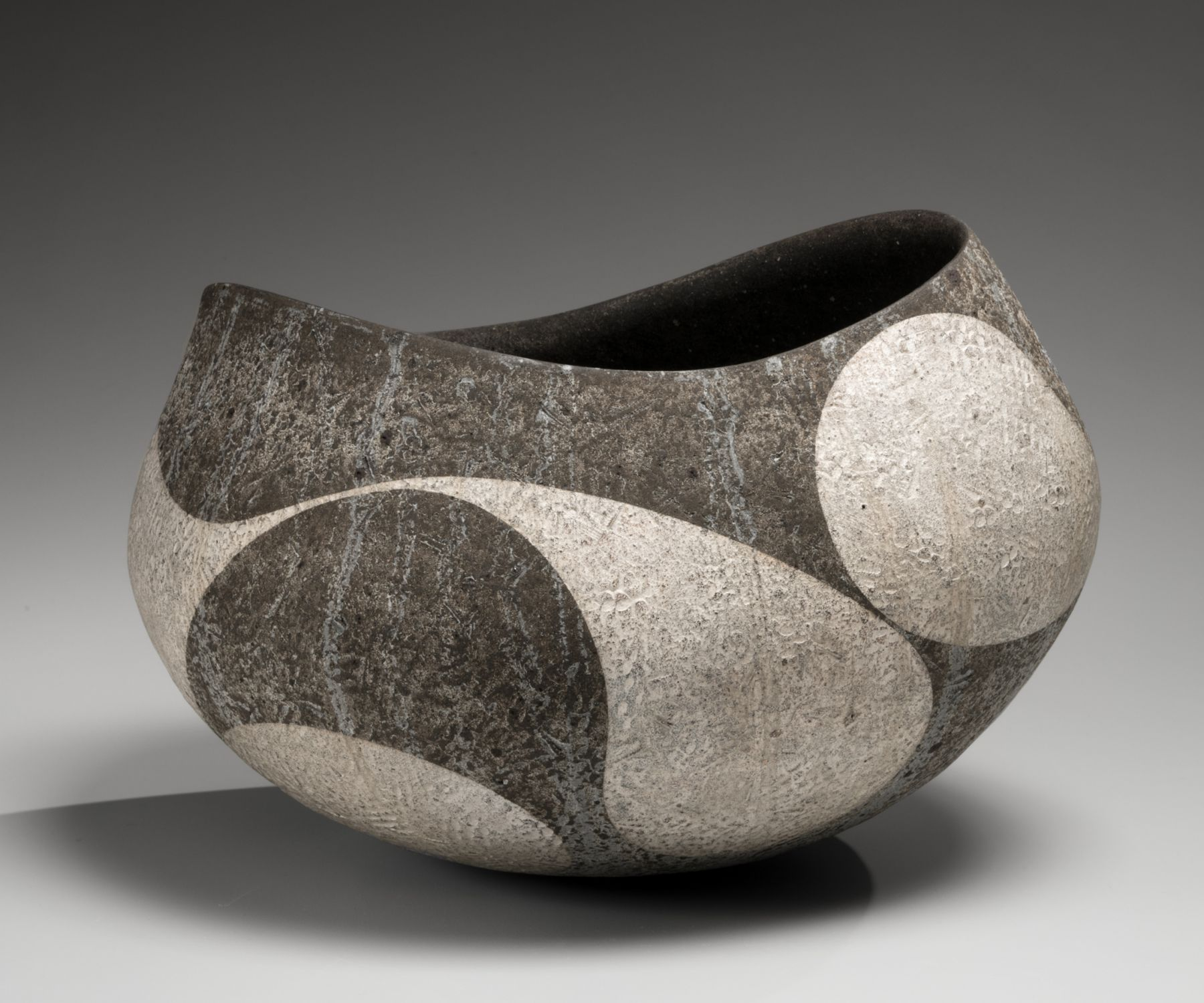 Iguchi Daisuke (b. 1975), Dark blackish-brown rounded vessel with wide open mouth and curvilinear patterning in silver slip
