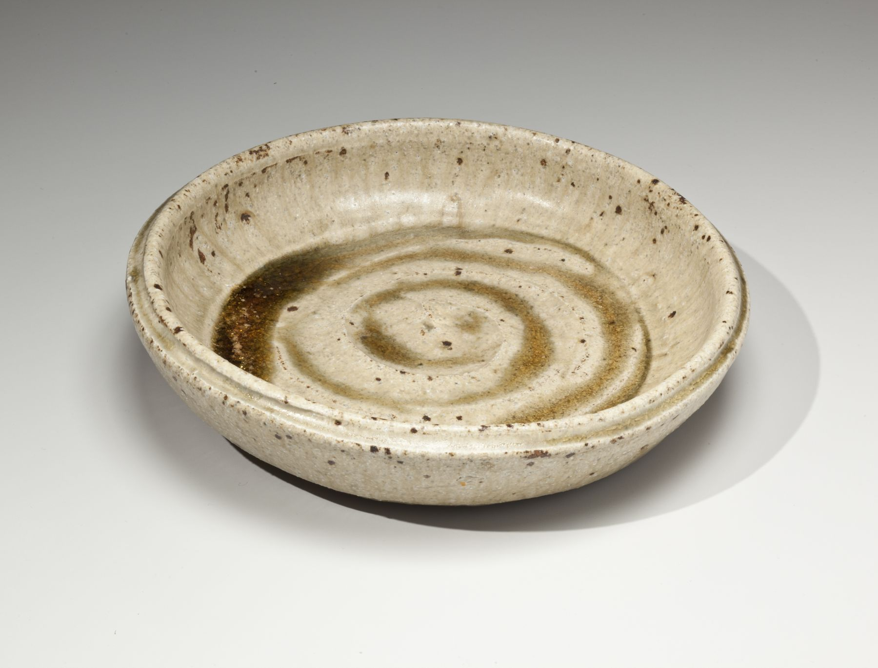 Kitaōji Rosanjin (1883-1959), Iga-glazed, round, cream colored vessel with natural green ash-glaze pooling in the central concentric rings