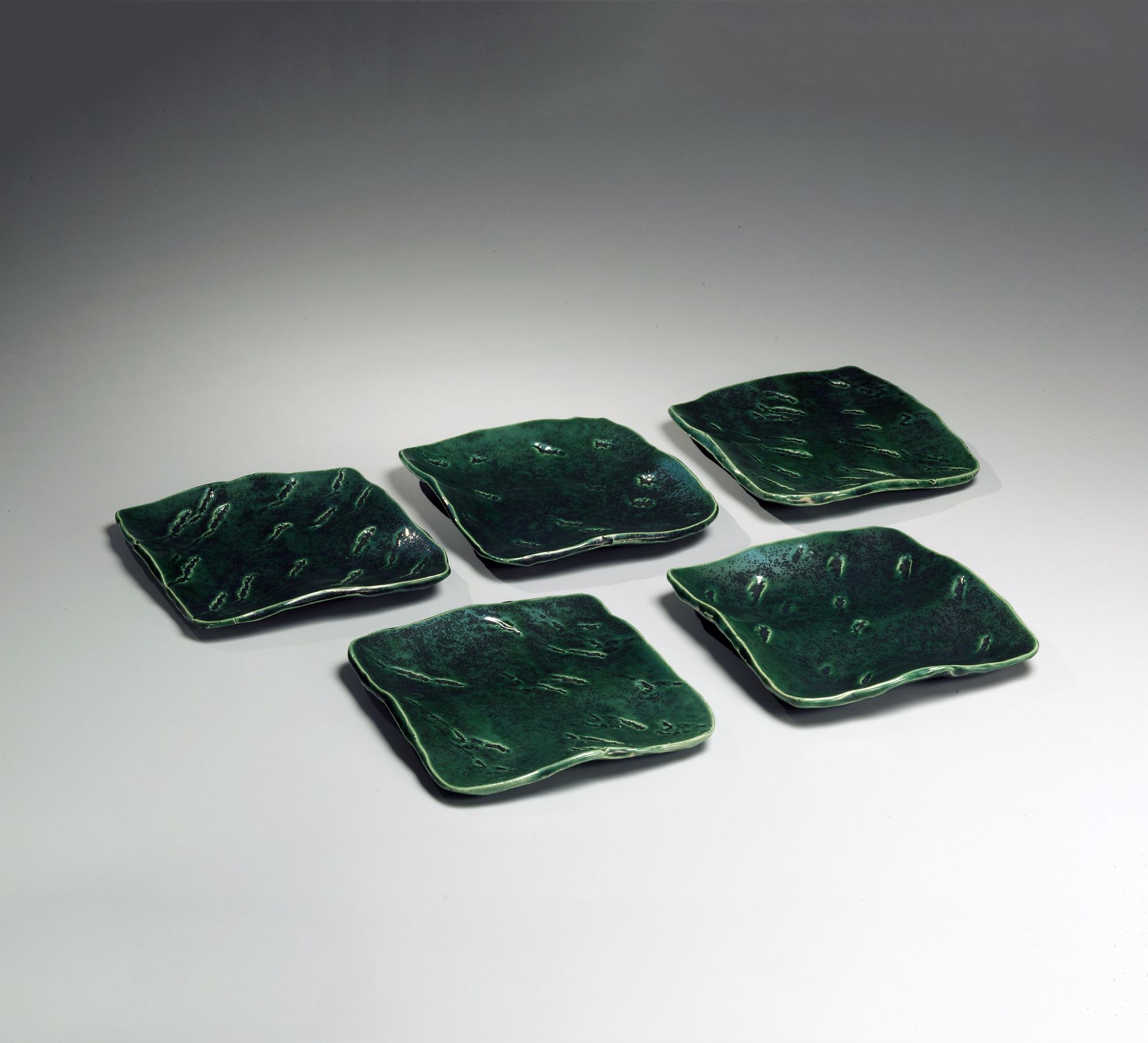 Hamanaka Gesson (b. 1943), Set of five square oribe-glazed plates with incisded decoration