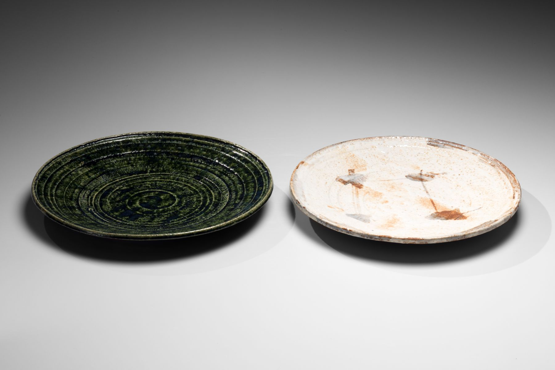 Okabe Mineo (1919-1990), Pair of circular platters, one with oribe-glaze and rings of concentric linear patterning and the other with shino-glaze and iron-glaze decoration