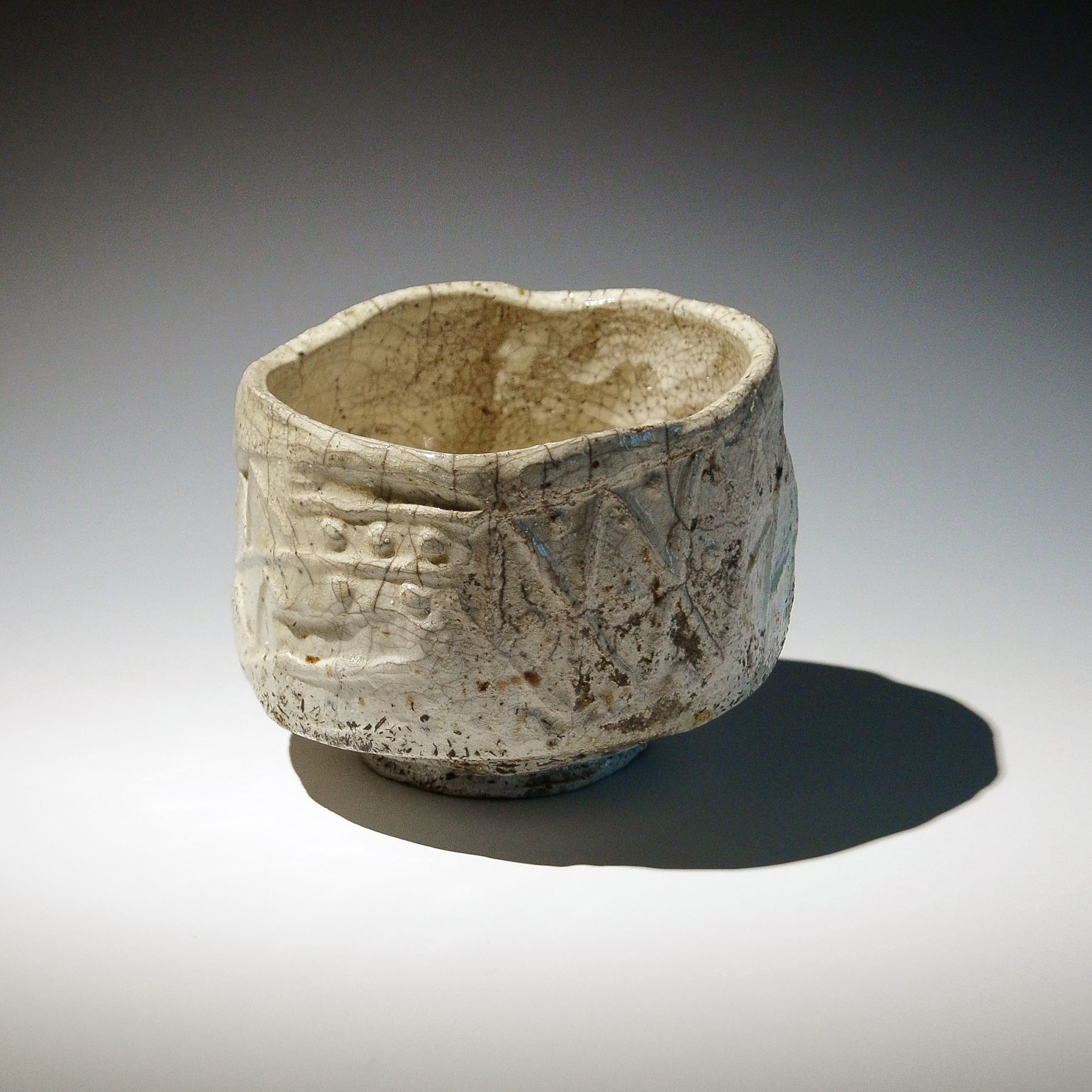 Tanimoto Kei (b. 1948), Large Iga white-glazed raku-style straight-sided teabowl with irregular mouth and carved patterning