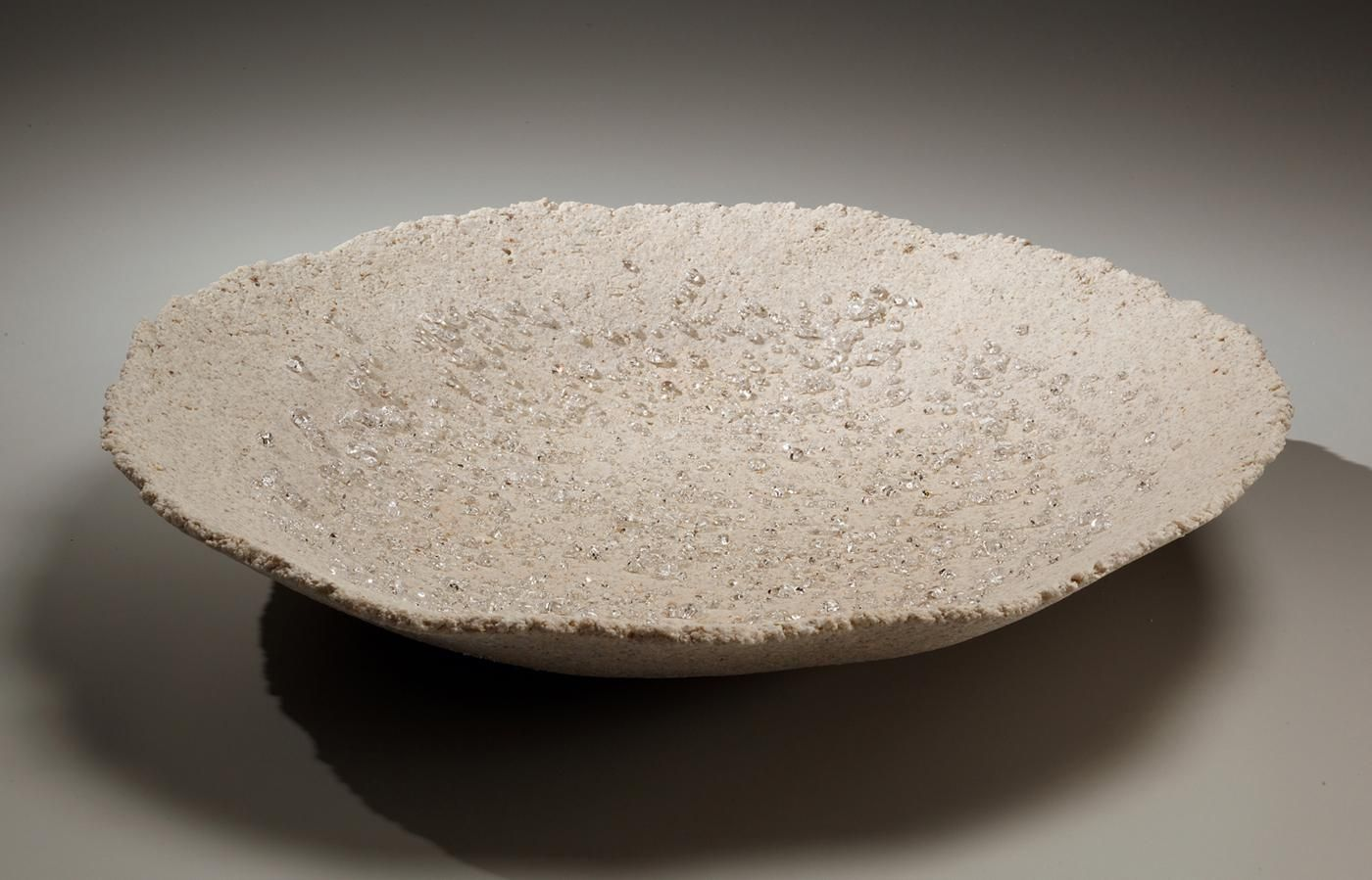 Round platter with scattered clear glass droplets and pinched rough rim, 2014