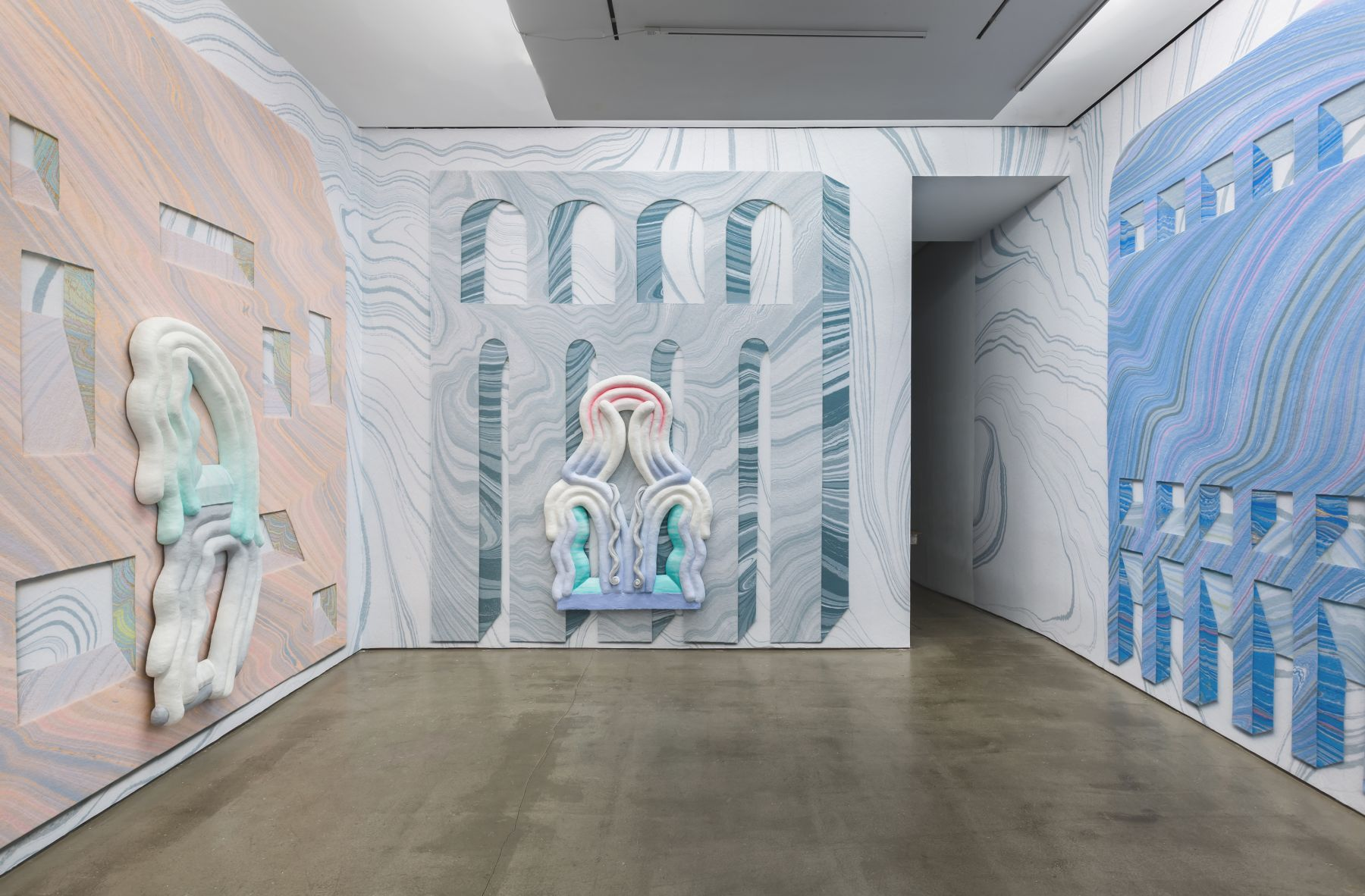 Installation view from Lauren Clay's solo exhibition. Large sculptural pieces hang on the wall. The wall is papered with custom-made wallpaper.