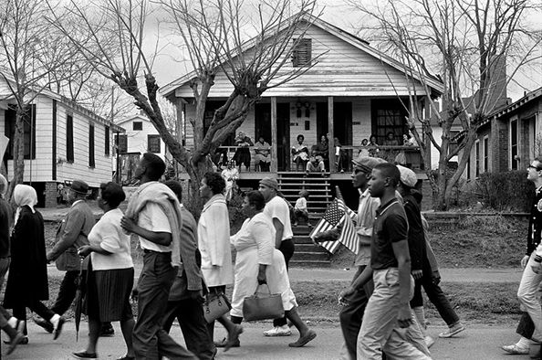 Selma to Montgomery civil rights marchers passing by house with people, African-American and white man holding small American flag in Montgomery, Alabama on March 25, 1965