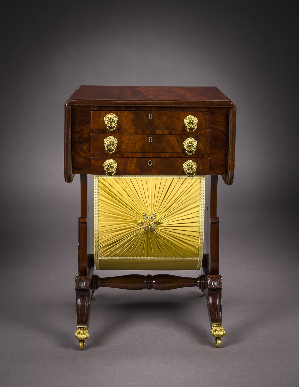 Neo-Classical Drop-Leaf Work Table with Lyre Ends, about 1828–29. Attributed to Rufus Pierce, Boston. Mahogany, with gilt-brass paw toe-caps and castors, drawer pulls, key-hole escutcheons, baize writing surface, and fabric on workbox, 28 13/16 in. high, 19 1/2 in. wide, 20 1/8 in. deep (at the castors). Frontal view.