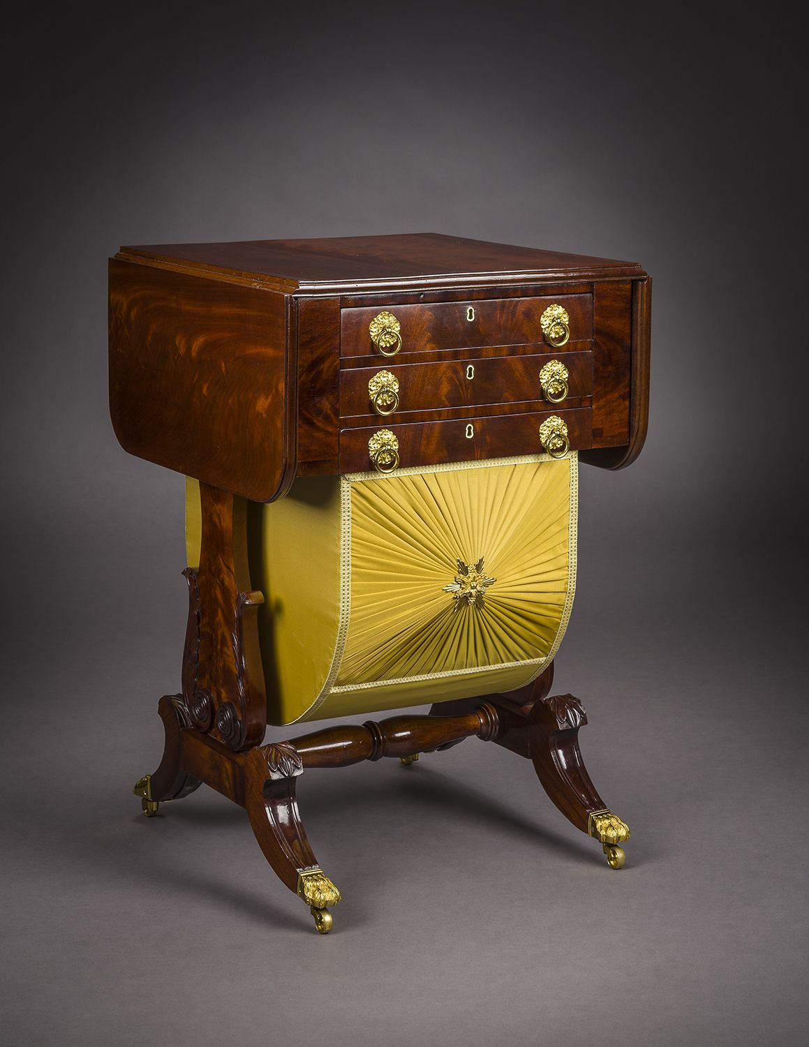 Neo-Classical Drop-Leaf Work Table with Lyre Ends, about 1828–29. Attributed to Rufus Pierce, Boston. Mahogany, with gilt-brass paw toe-caps and castors, drawer pulls, key-hole escutcheons, baize writing surface, and fabric on workbox, 28 13/16 in. high, 19 1/2 in. wide, 20 1/8 in. deep (at the castors). Oblique view with leaves down.