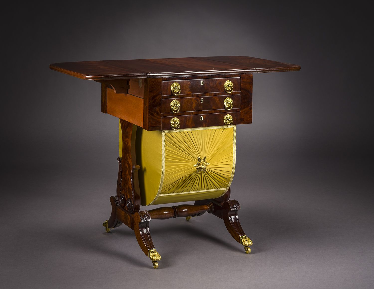 Neo-Classical Drop-Leaf Work Table with Lyre Ends, about 1828–29. Attributed to Rufus Pierce, Boston. Mahogany, with gilt-brass paw toe-caps and castors, drawer pulls, key-hole escutcheons, baize writing surface, and fabric on workbox, 28 13/16 in. high, 19 1/2 in. wide, 20 1/8 in. deep (at the castors). Oblique view with leaves extended.