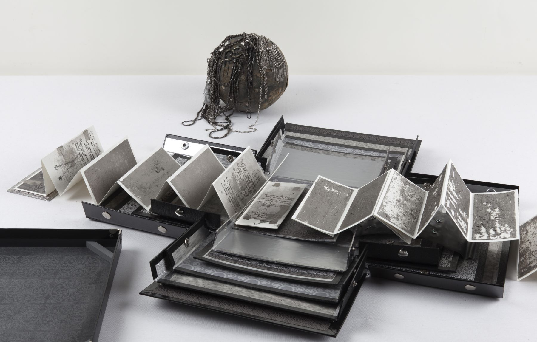 Silver, 2011 Aged silver metallic paper, paper, lead, necklaces, chain, bell, trinkets, one leporello book