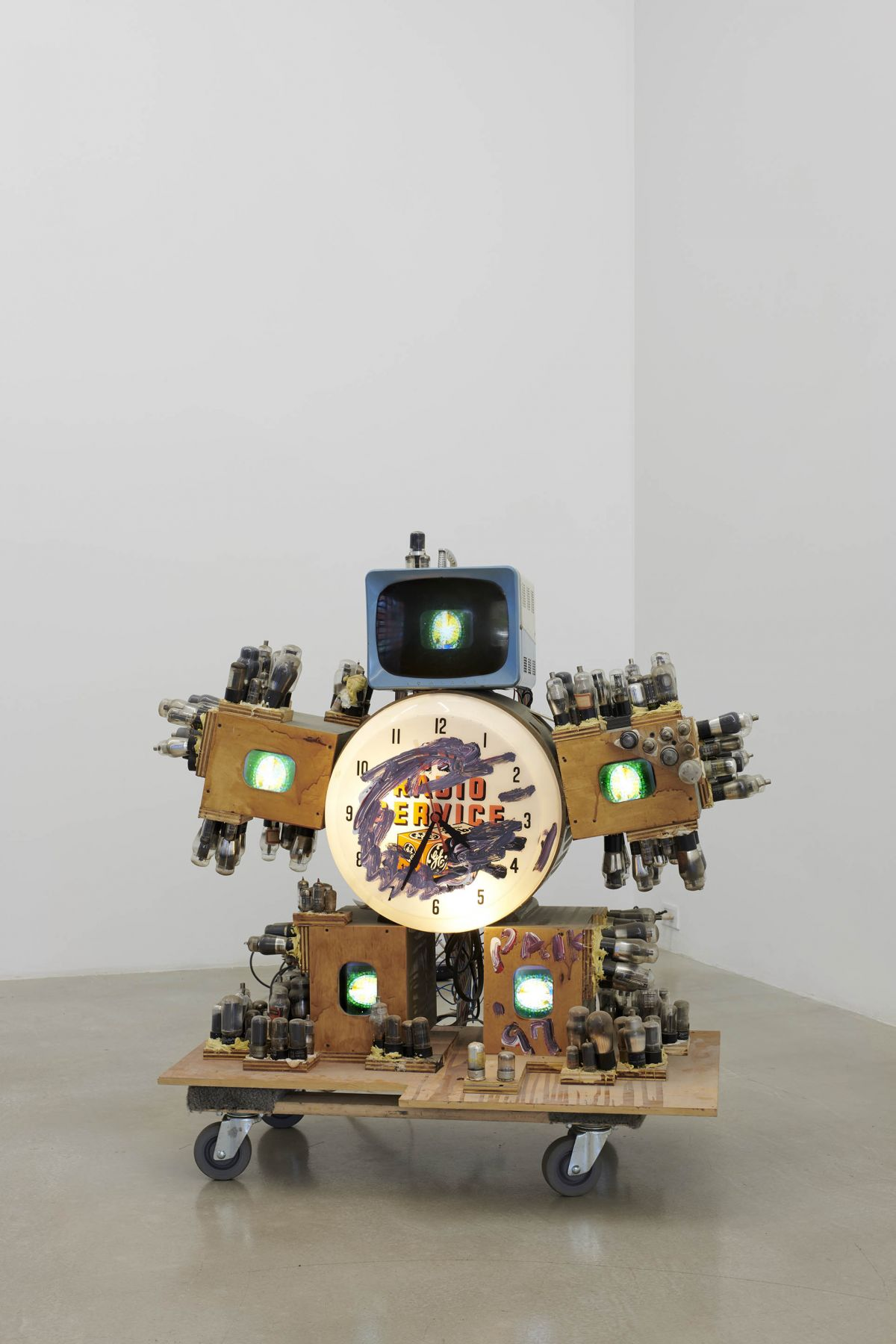 Five small televisions mounted around a clock, on wheels