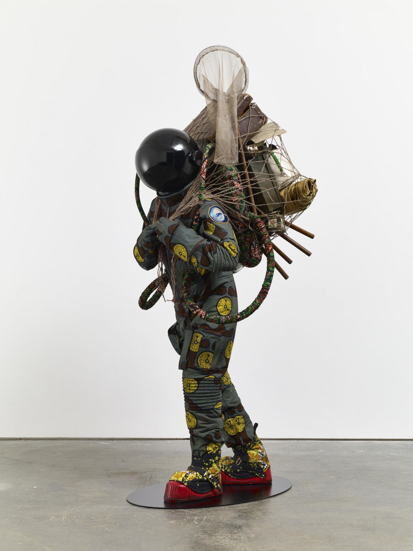 , YINKA SHONIBARE, MBE Refugee Astronaut, 2015 Fibreglass mannequin, Dutch wax printed cotton textile, net, possessions, astronaut helmet, moon boots and steel baseplate 81 7/8 x 36 9/16 x 35 3/8 in. (208 x 93 x 90 cm)