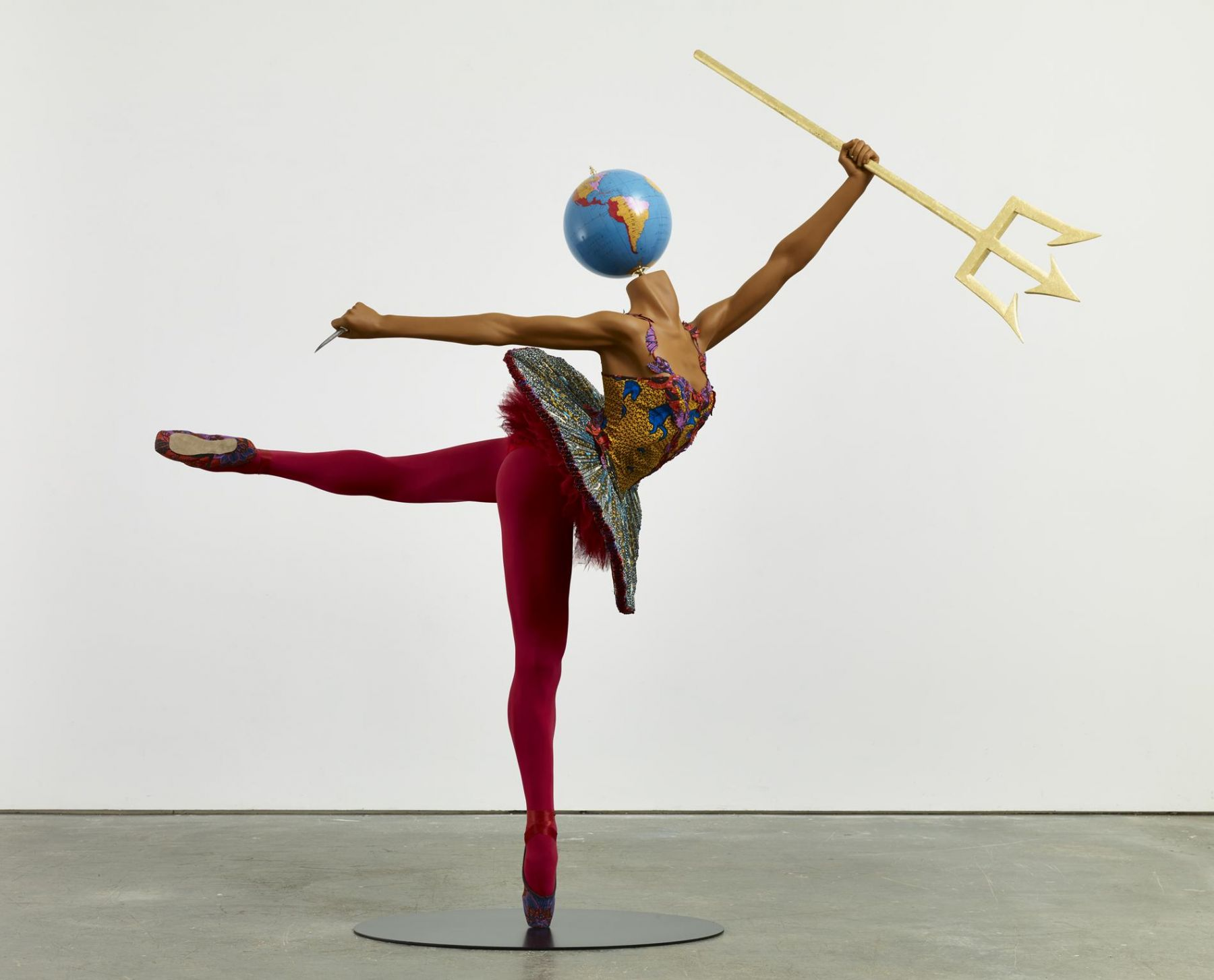 , YINKA SHONIBARE, MBE Ballet God (Poseidon), 2015 Fibreglass mannequin, Dutch wax printed cotton textile, trident, dagger, globe, pointe shoes and steel baseplate 82 1/4 x 87 x 35 3/8 in. (209 x 221 x 90 cm)