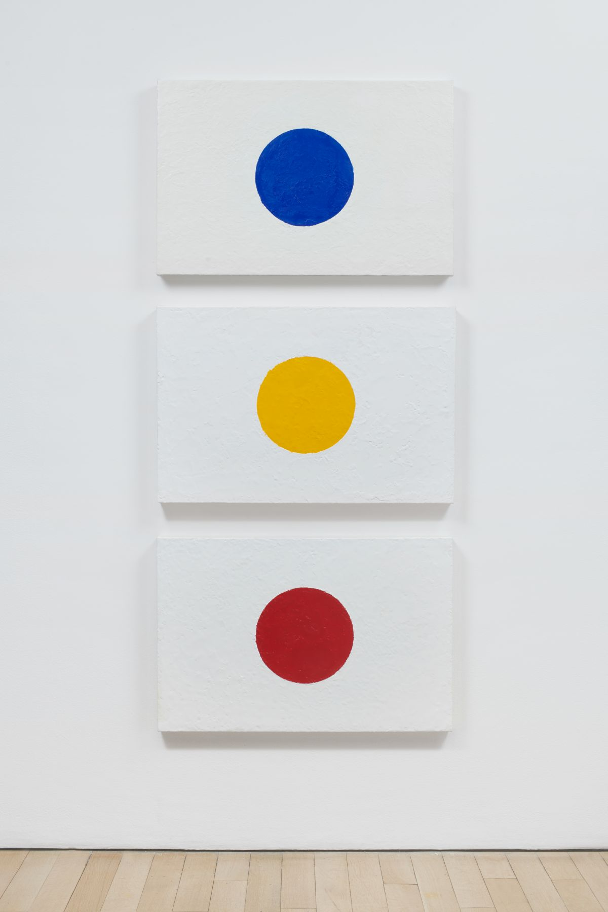 Three white canvases, each with a circle of a different primary color
