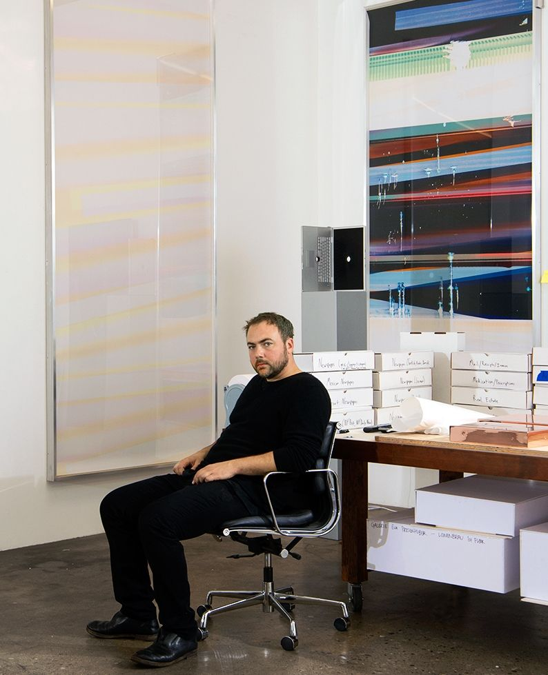 Portrait of Walead Beshty sitting in a desk chair with two giant curl pieces hanging on the walls behind him.