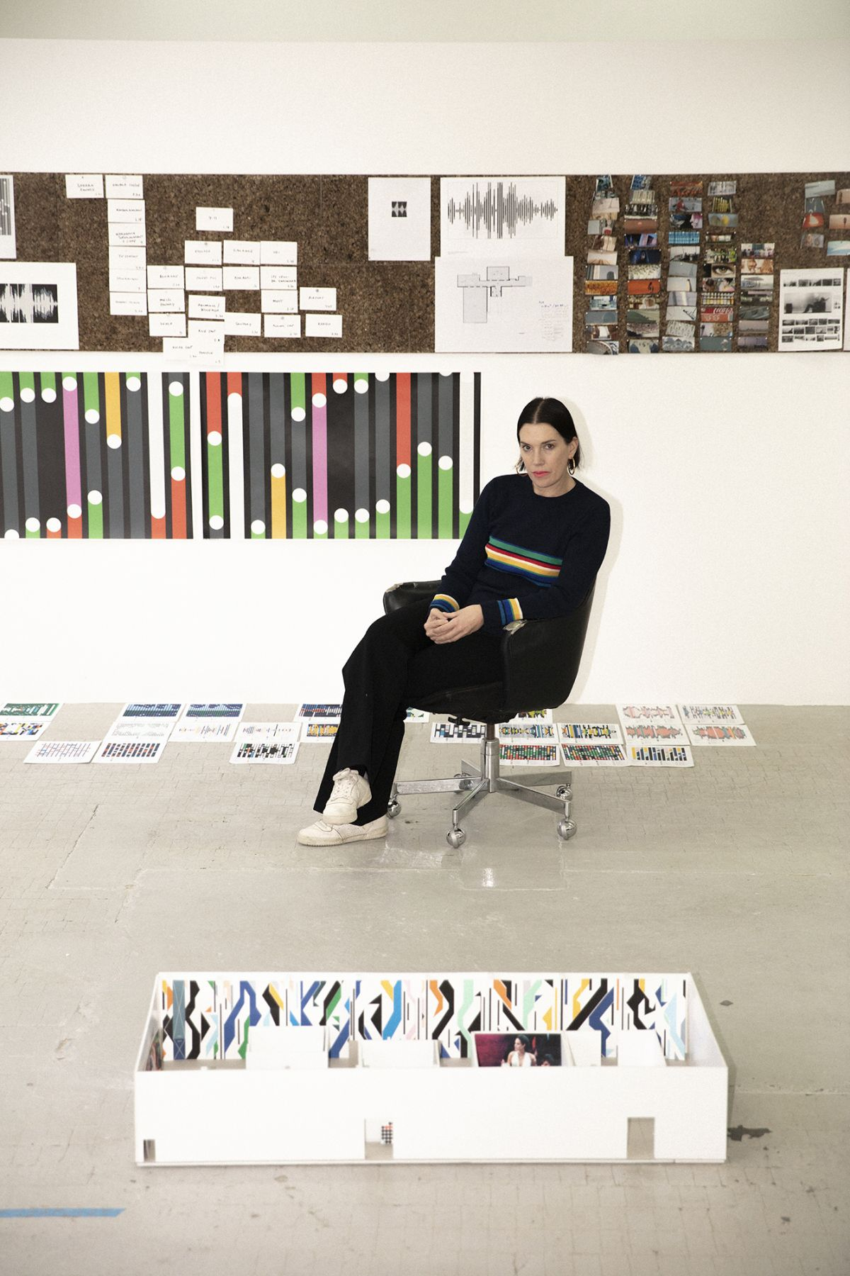 A portrait of Sarah Morris sitting in her studio