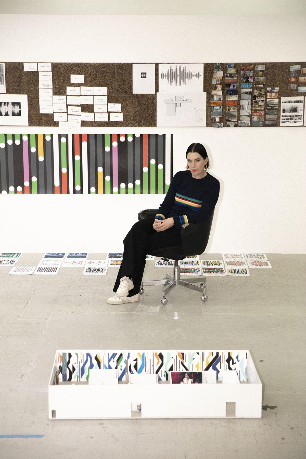 A portrait of Sarah Morris sitting in her studio