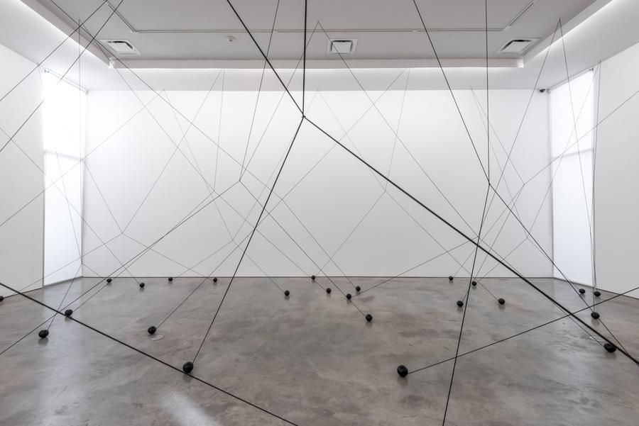 Magdalena Fernández, 2i000.017, 2017. Iron spheres with black elastic cord, variable dimensions