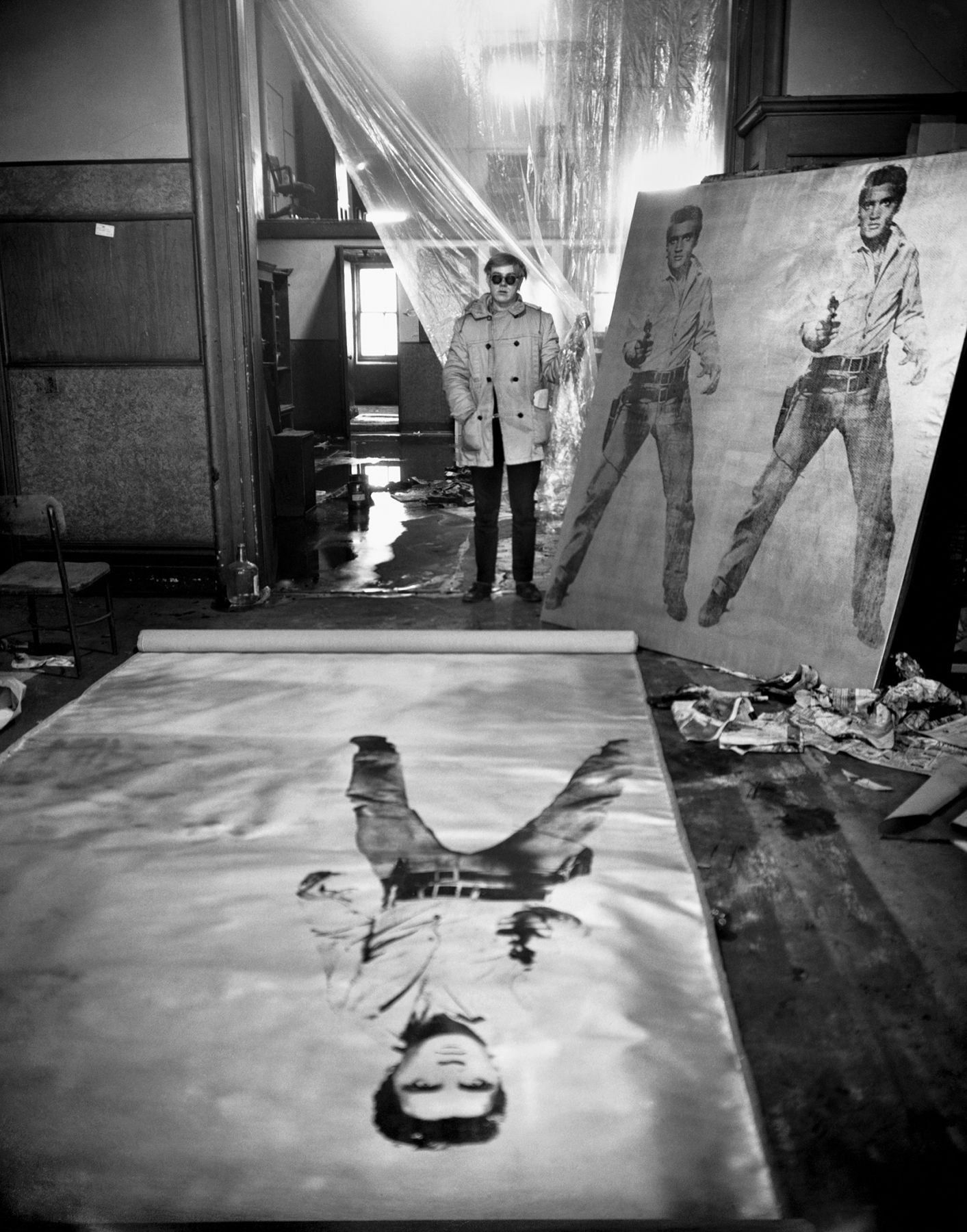 Andy Warhol (In his studio with Elvis Presley Print), New York. 1962, 20 x 16 inch gelatin silver print