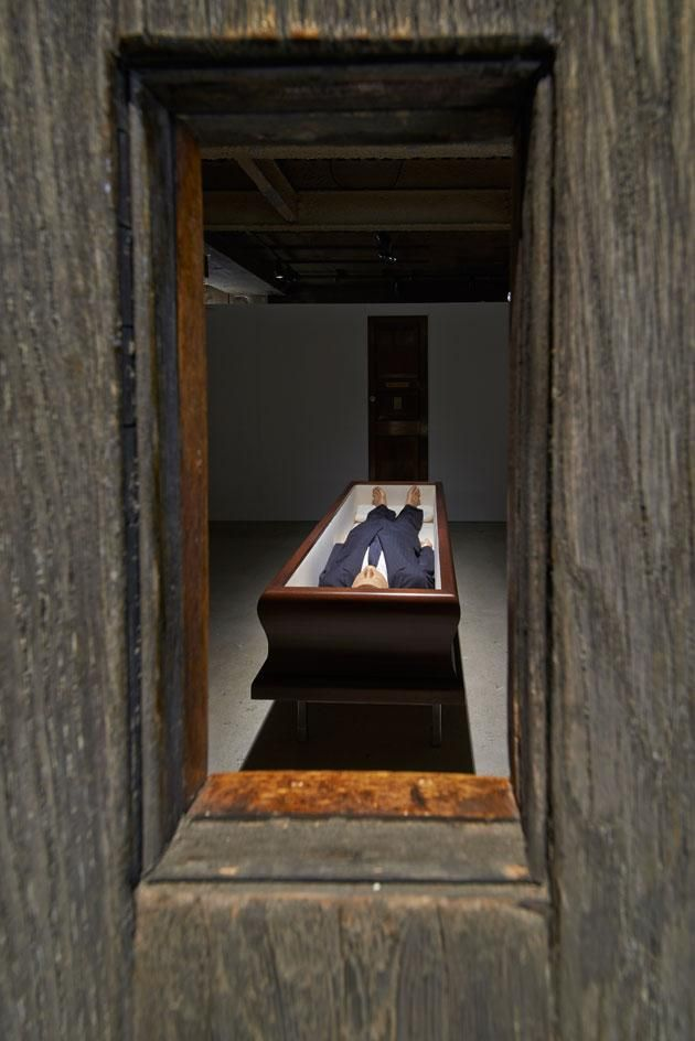 The space is split into seven rooms, with dark-painted walls creating mysterious chambers, each containing a single piece. Pictured is 'Now', 2004