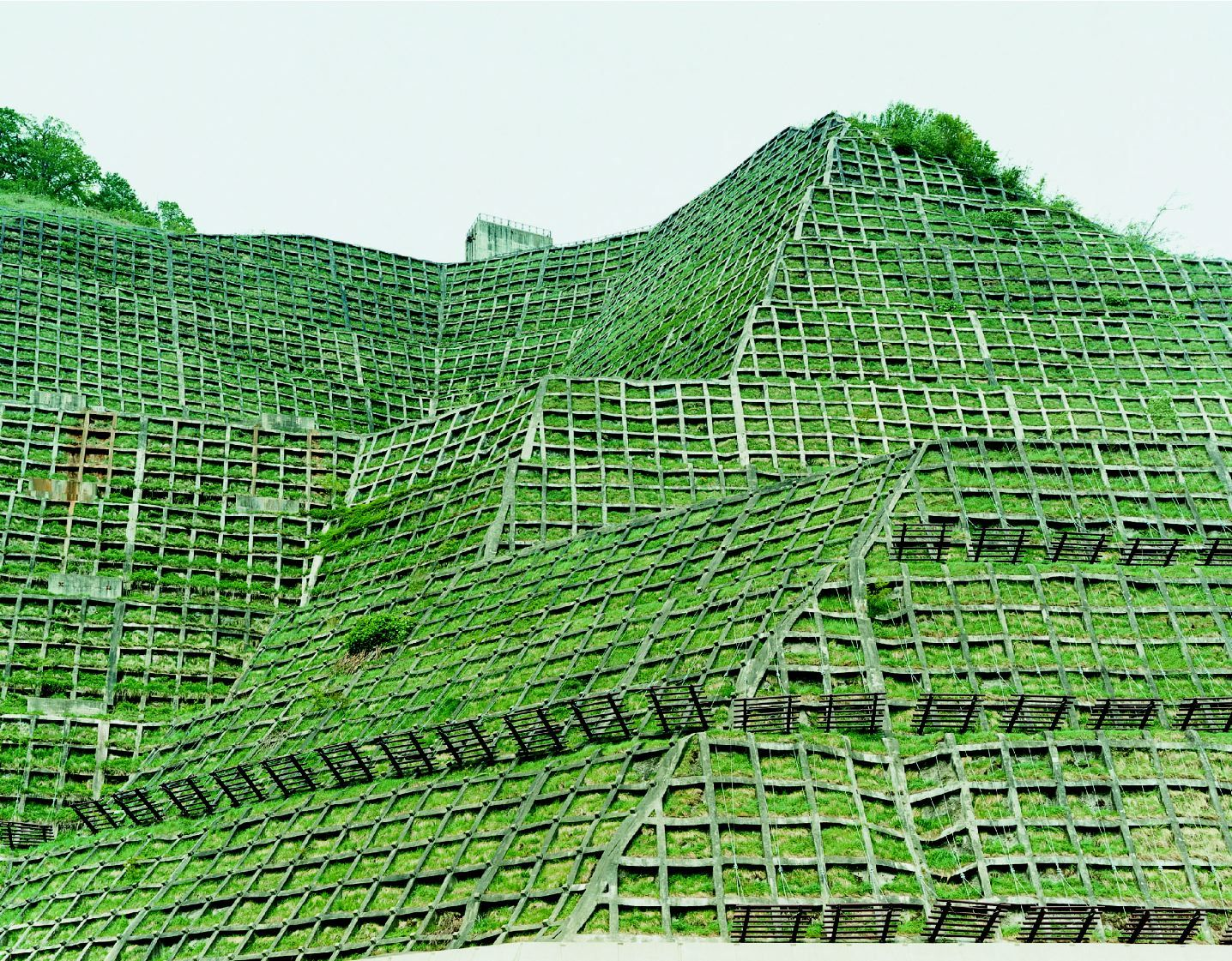 photo of grassy hill with architecture by thomas fletchner