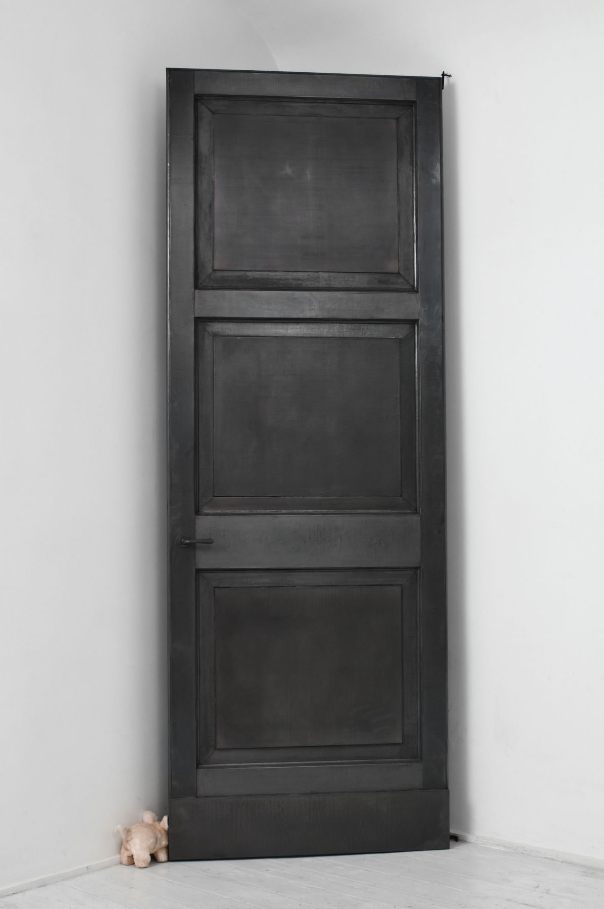 black door with small toy by pier paolo calzolari