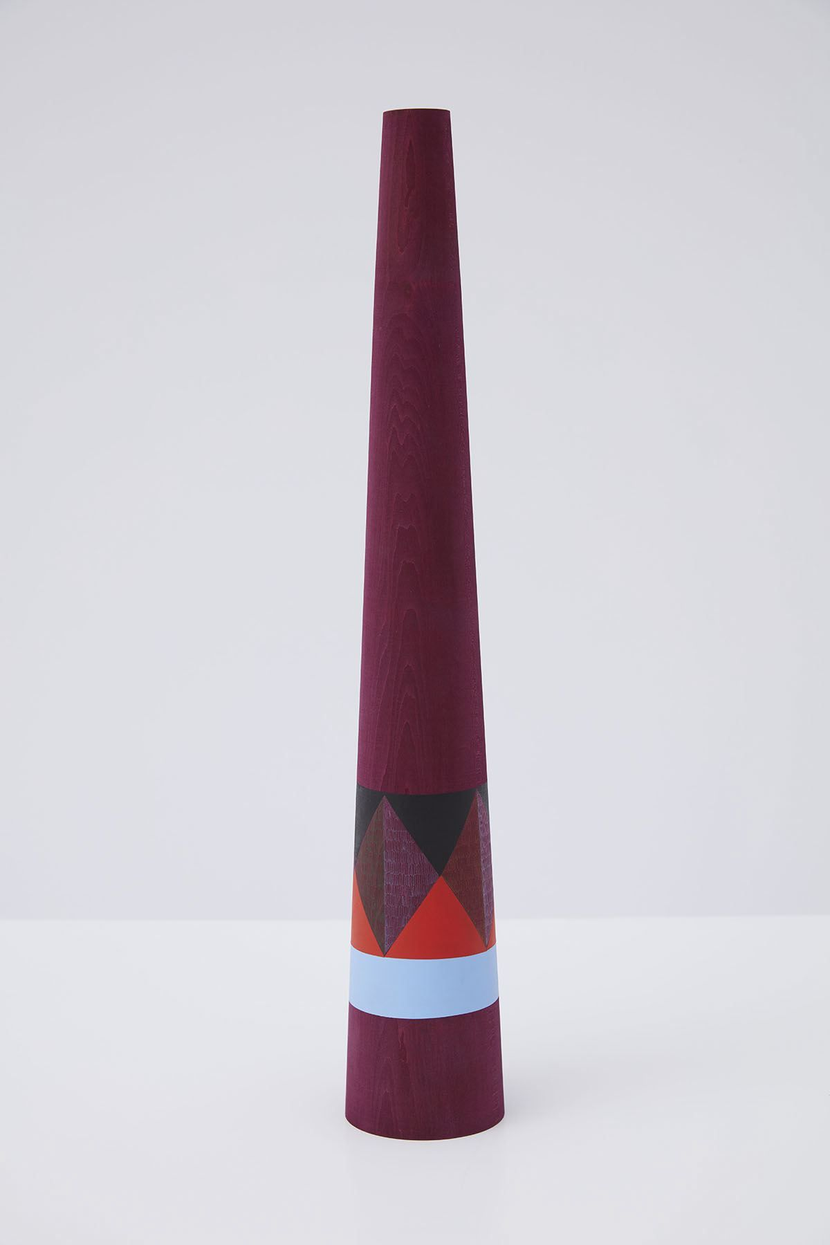 wooden sculpture with geometric shapes painted on it by claudia wieser