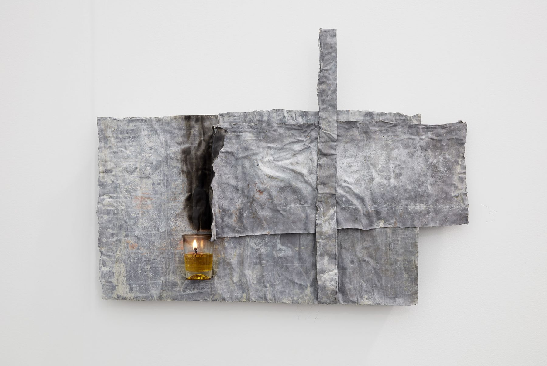 a lead and candle work of art by Italian artist Pier Paolo Calzolari