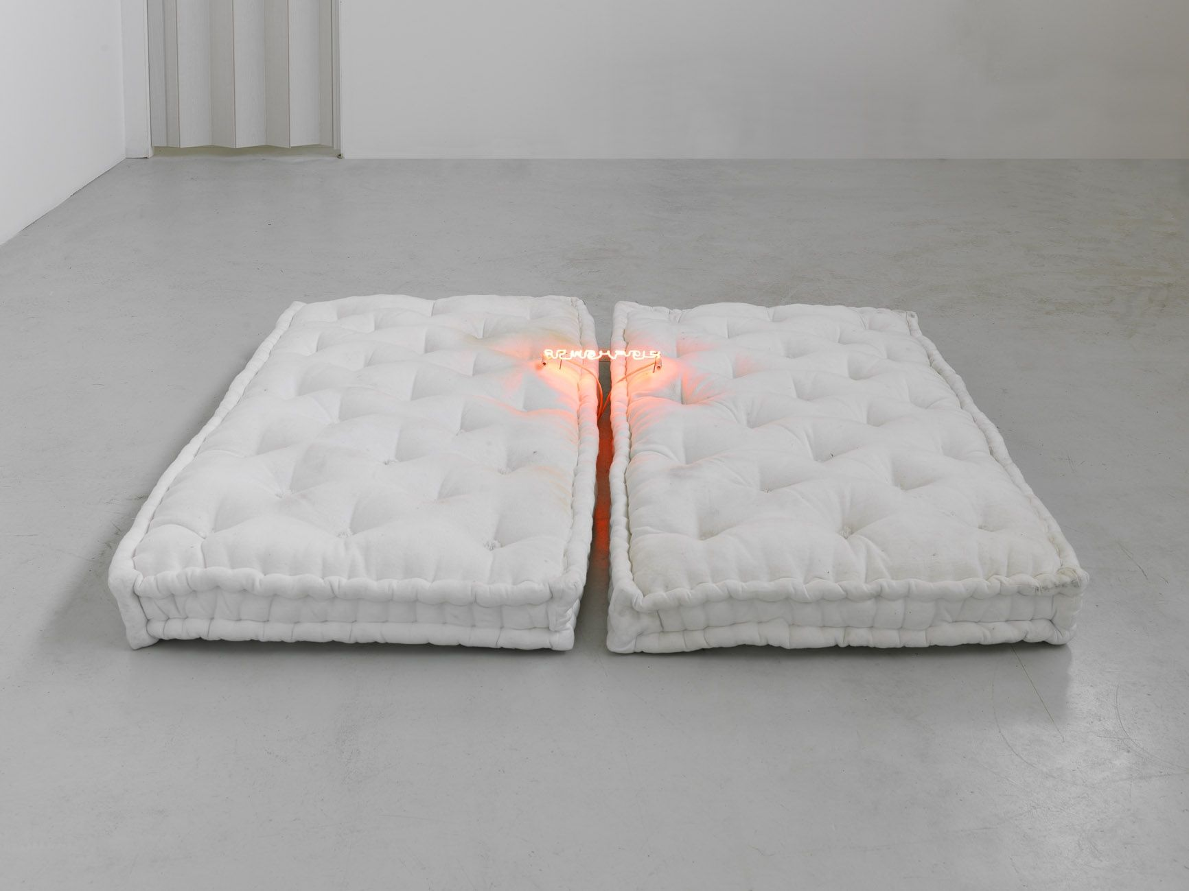 a contemporary sculpture with neon lights and a mattress by Pier Paolo Calzolari