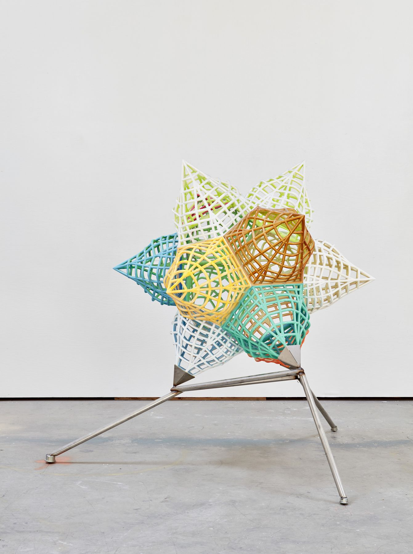 a metal 3 dimensional star in bright colors by artist frank stella and exhibited in a gallery