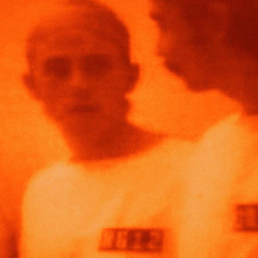 orange photograph of a man looking at himself in the mirror by kon trubkovich