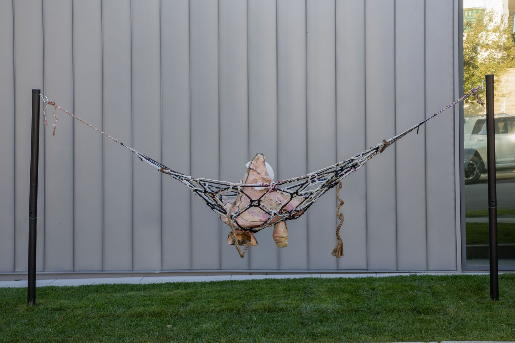 a ceramic artwork in a hammock that is exhibited outdoors by jessica jackson hutchins