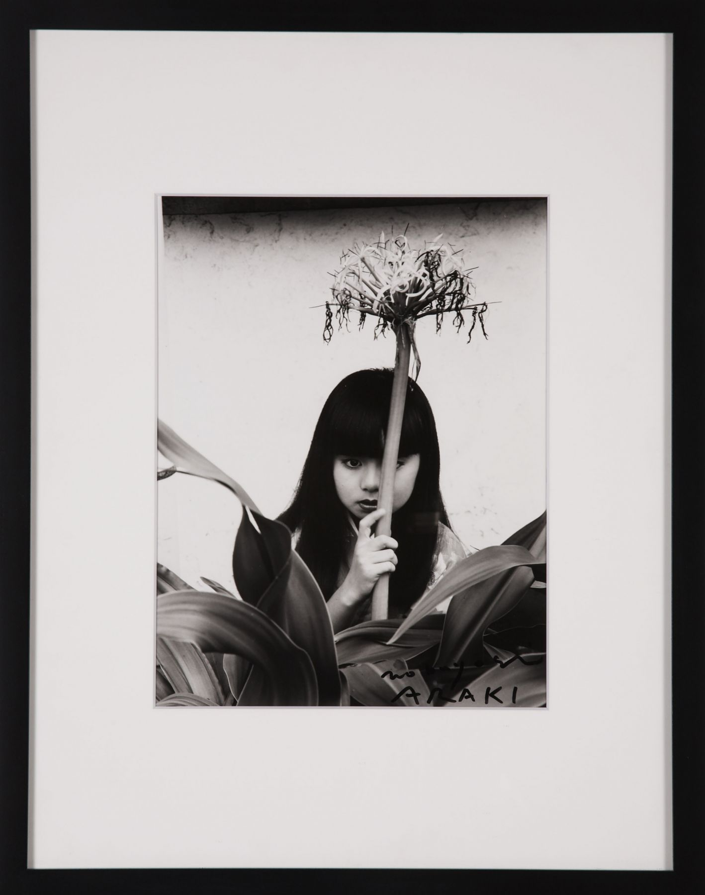 photo of a girl with a flower by nobuyoshi araki