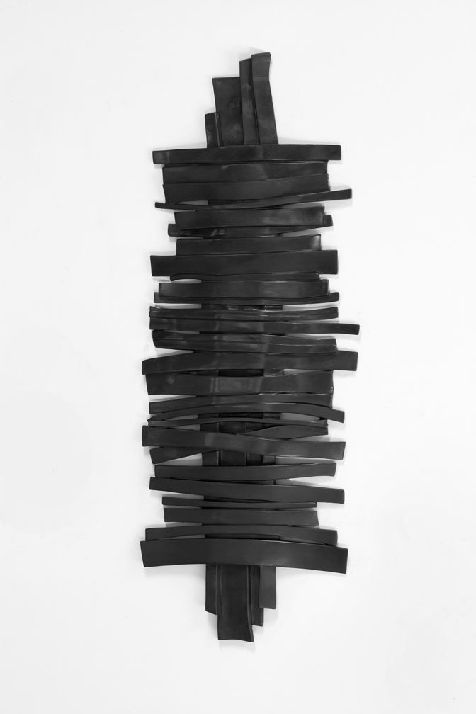 a bronze wall sculpture of horizontal strips overlaying a vertical strip by anthony pearson