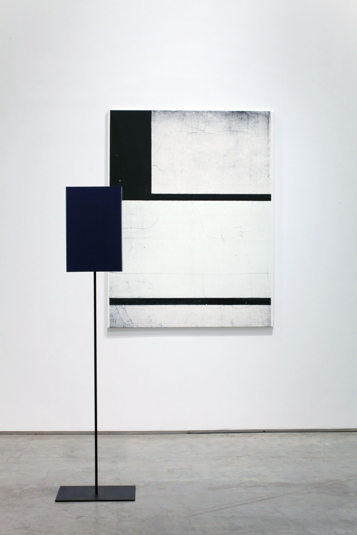 installation by melissa gordon with white and black grid painting and blue rectangular sculpture