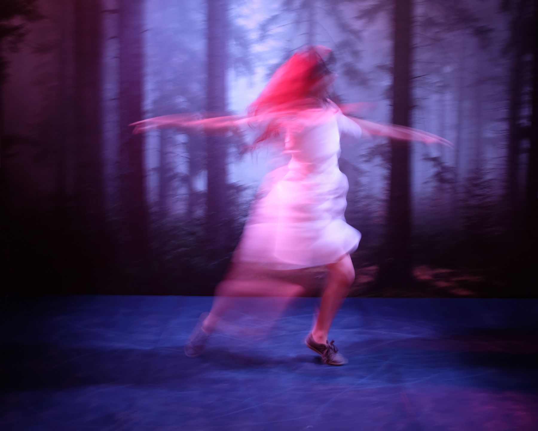 a woman spinning in a forest from a video by sue de beer in an art gallery