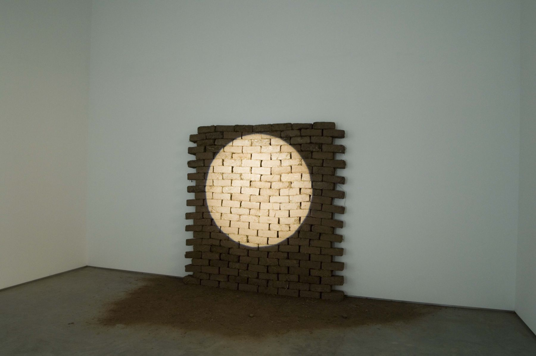 installation with bricks highlighted by a spotlight by christ moukarbel