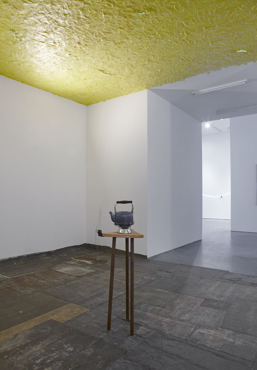installation by pier paolo calzolari featuring a teapot on a wooden pedestal and a yellow, waxy ceiling