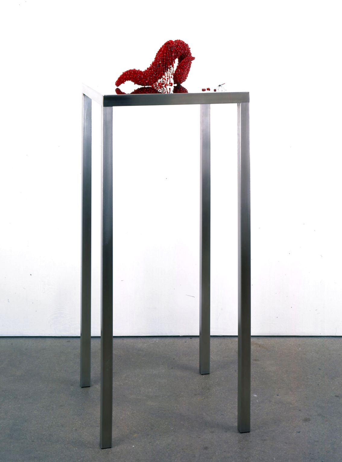 Black table with red sculpture by Angelo Filomeno