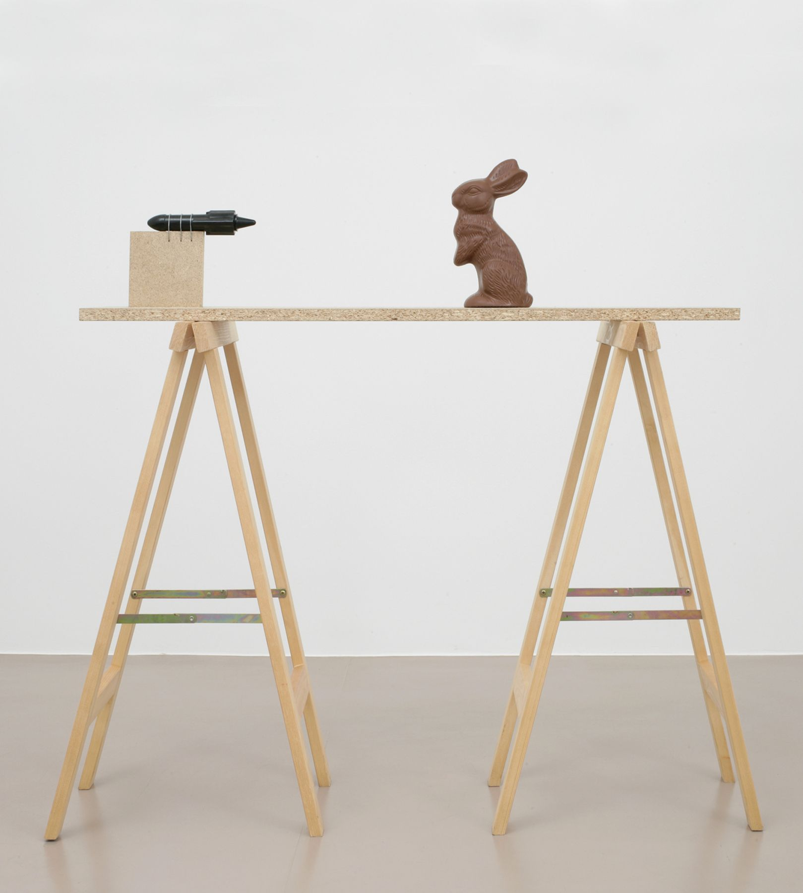 installation by roman signer featuring a rocket aimed at a chocolate easter bunny