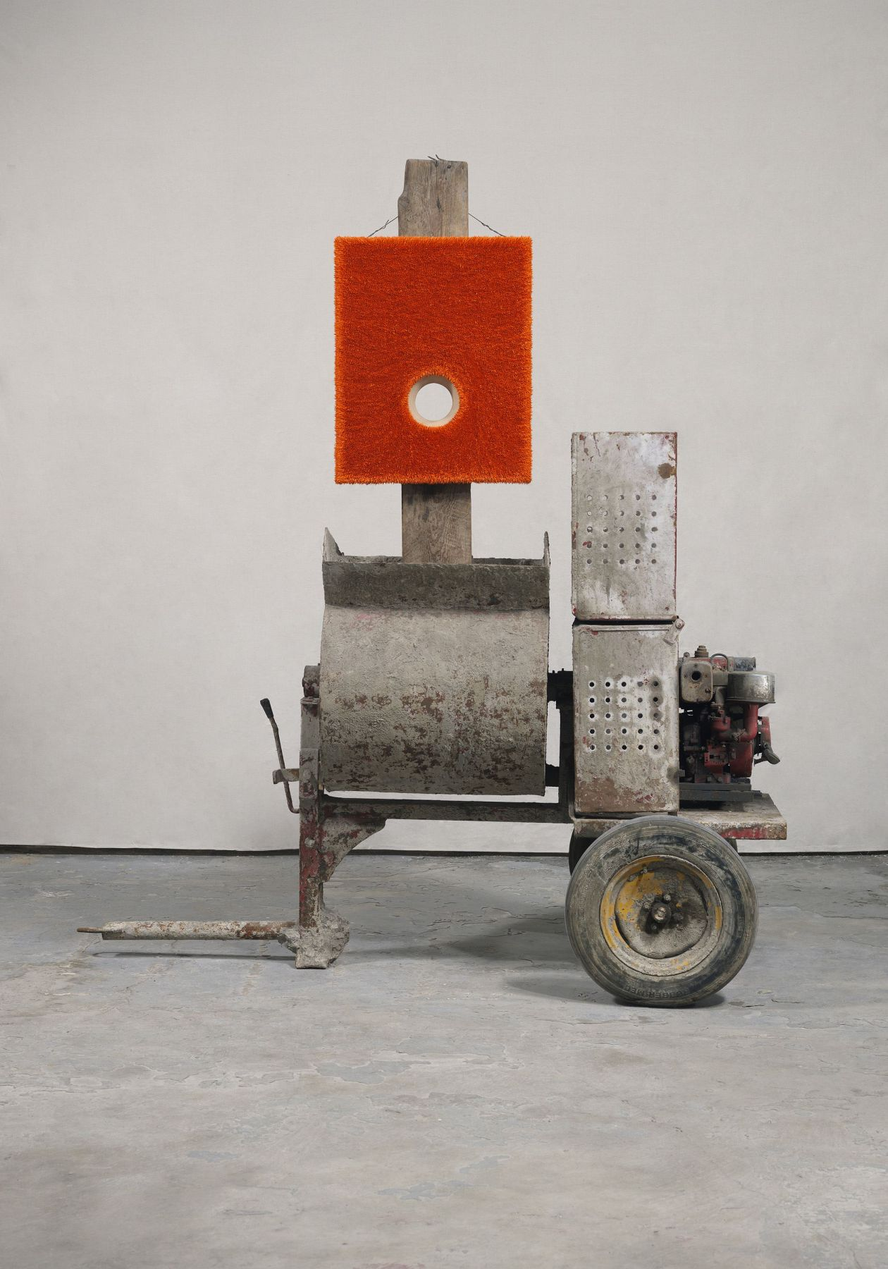 mixed media sculpture by donald moffett with red panel, tire, and concrete