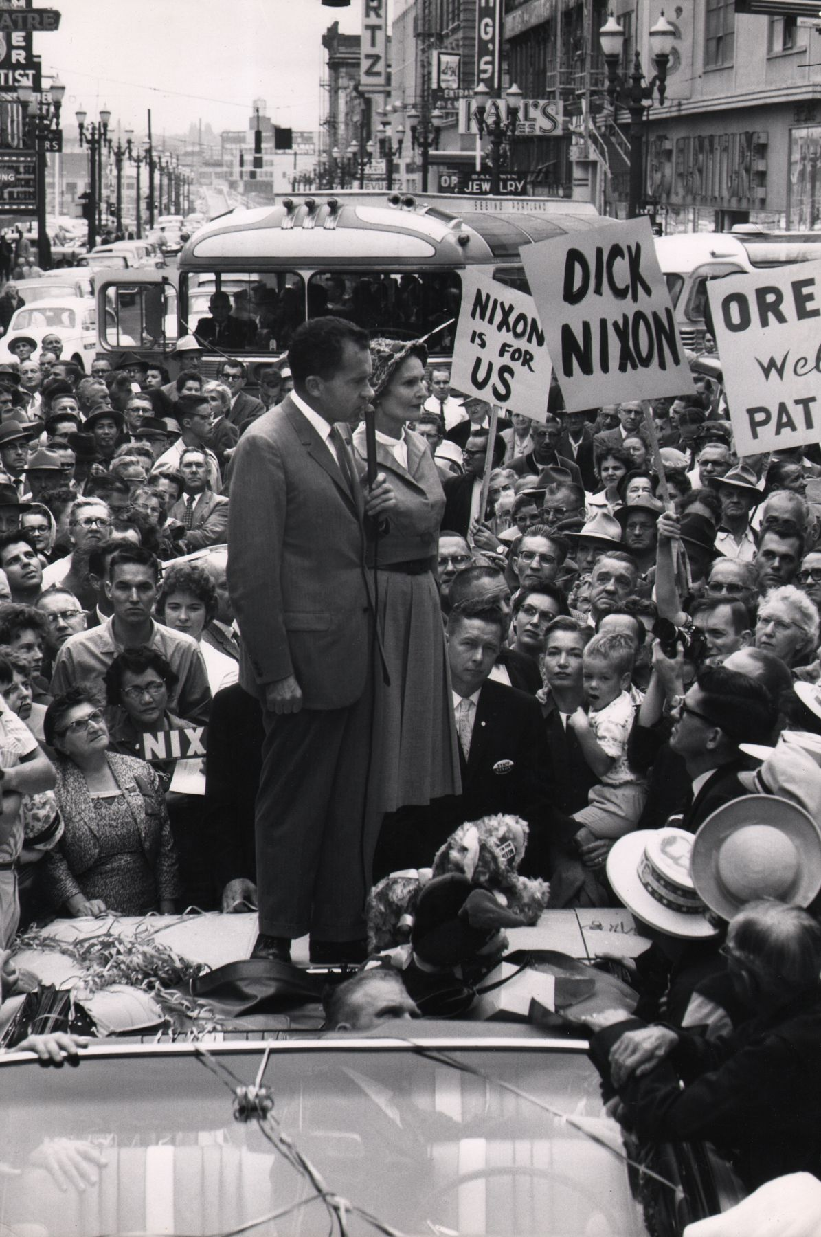 """Ed Clark, Nixon campaigning in the 1960 presidential election, 1960. Subject stands on the back of a car speaking into a microphone surrounded by a large crowd holding signs such as """"Nixon is for us"""" and """"Dick Nixon"""""""